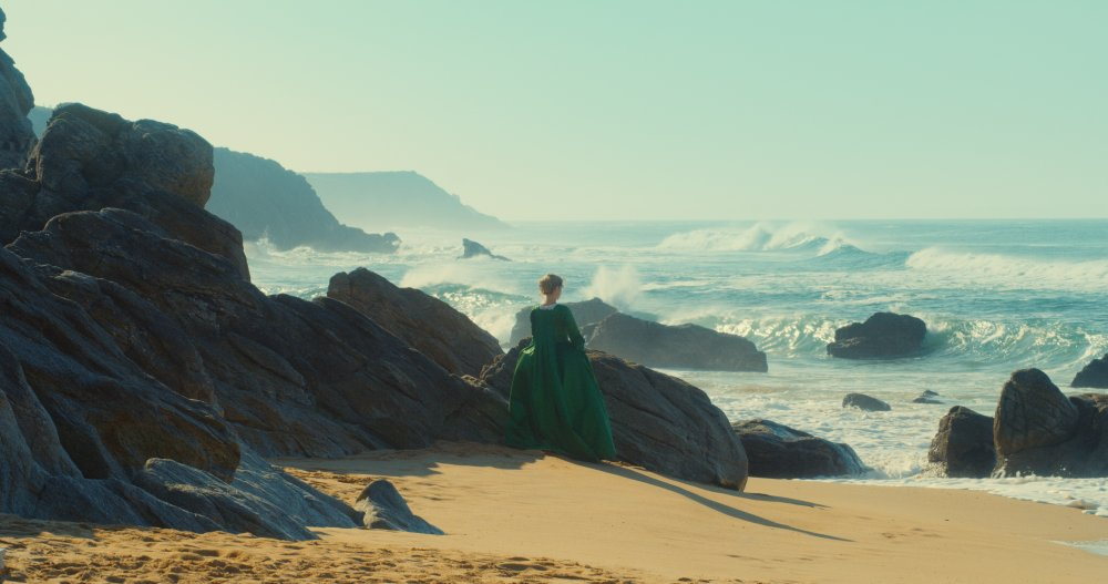 portrait-of-a-lady-on-fire-2019-002-woman-in-green-dress-against-rocky-shore-ORIGINAL